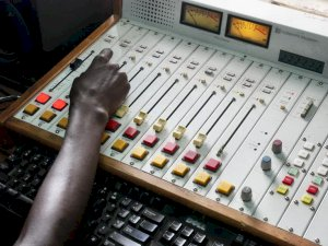 Photo is a closeup of hand at a set of audio controls