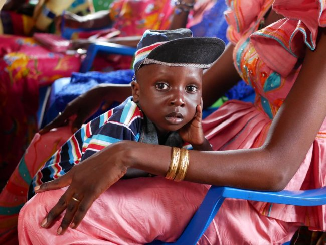 A Senegalese boy resting in his mother's arms as she watches during a community video dissemination event.