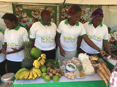 "Photo of four women wearing SPRING tee shirts presenting a table of health foods. Caption: ""SPRING booth displaying healthy foods at the launch of the micronutrient powder pilot project in Namutumba District."""